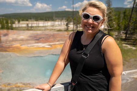 Pretty blond woman tourist poses in front of Firehole Spring in Yellowstone National Park, wearing white sunglasses 版權商用圖片