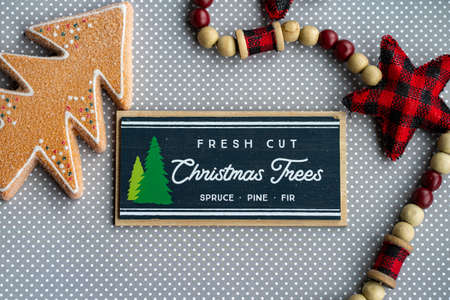 Fresh cut Christmas trees sign with red plaid fabric stars and gingerbread tree on grey polka dot background, for Christmas projects 版權商用圖片