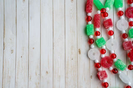 Sugar Christmas candy garland on a white wood background, right aligned, useful for holiday backgrounds