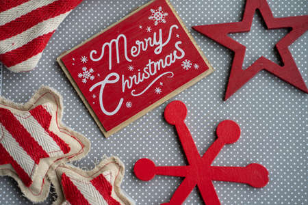 Merry Christmas red flatlay with wood and fabric snowflake decorations on a gray and white polka dot background