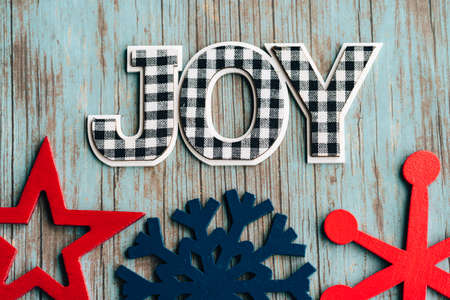 Black and white plaid Joy word letters with blue and red wood snowflakes on a teal wood background, useful for rustic Christmas holiday projects 版權商用圖片