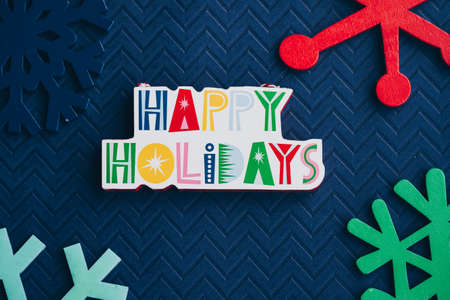 Happy Holidays plaque message and colorful wooden snowflakes on blue background, for Christmas projects 版權商用圖片