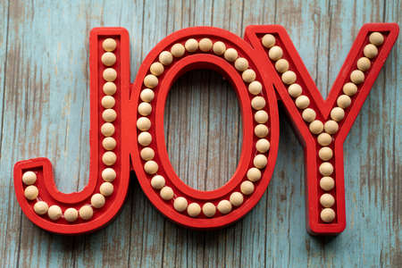 Red Joy word letters on a teal wood background, useful for rustic Christmas holiday projects