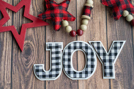 Black and white joy plaid phrase on a wood background with red stars, useful for Christmas projects
