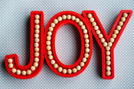 Red Joy word letters on a gray white polka dot wood background, useful for rustic Christmas holiday projects