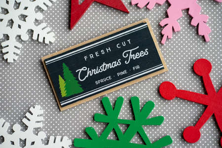 Fresh cut Christmas trees plaque, diagonal, with red green and pink wood snowflakes on gray and white polka dot background