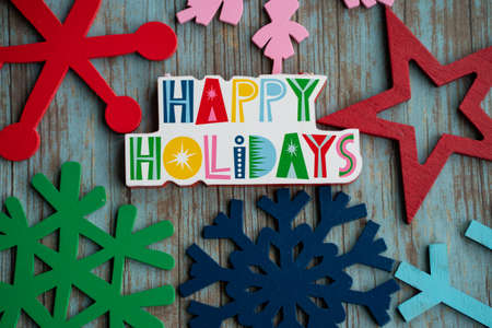 Happy Holidays with rainbow colored snowflakes, on a teal wood background. Useful for Christmas projects