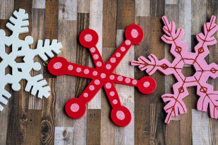 White, red and pink glitter wooden snowflakes on a brown wood plank background. Useful for rustic Christmas holiday projects