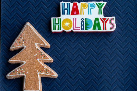 Happy Holidays plaque message and a glitter gingerbread Christmas Tree on blue background 版權商用圖片
