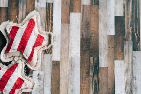 Rustic fabric red and beige stars on a wood plank background, useful for Christmas holiday projects