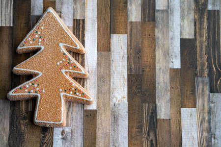 Sugary gingerbread cookie tree on a wood plank background, useful for Christmas holiday projects