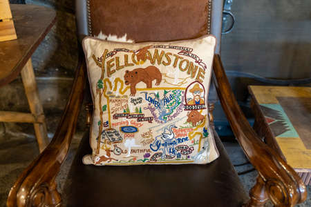 Wyoming, USA - September 25, 2020: Detaiiled, embroidered throw pillow sitting on a wooden chair, in Yellowstone National Park