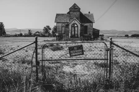 Old, abandoned LDS mormon church in Ovid, Idaho. No trespassing sign and fence Stock Photo