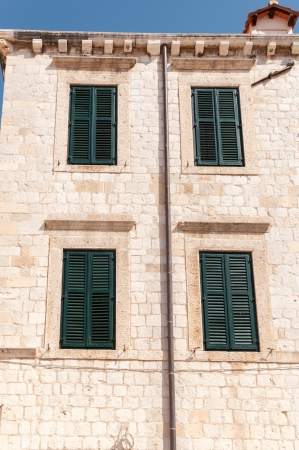 Framed ancient windows with green shutters in a rows  photo