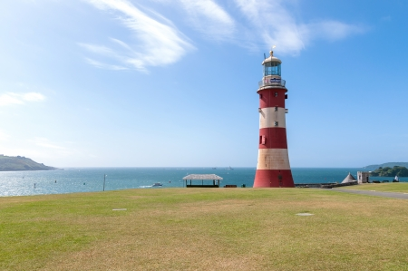 lighthouse with beam: Red and white lighthouse in Plymouth, Great Britain Stock Photo