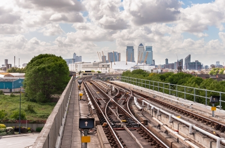 The railway tracks of Docklands Light Railway with Canary Wharf skyscrapers in the background