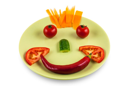 Smiling face made of vegetables on green plate isolated over white background with clipping path  photo