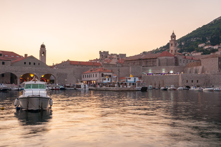 Boats moored in old town pier of Dubrovnik at sunset photo