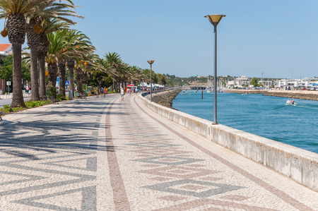LAGOS, PORTUGAL - SEPTEMBER 1: Palm Trees along the beautifully paved promenade on 1 September, 2014 in Lagos. Lagos is one of the most visited cities in the Algarve and Portugal.