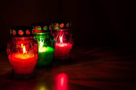 Closeup of colored burning votive candles in the dark photo