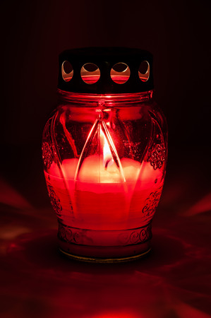 votive candle: Closeup of red burning votive candle in the dark