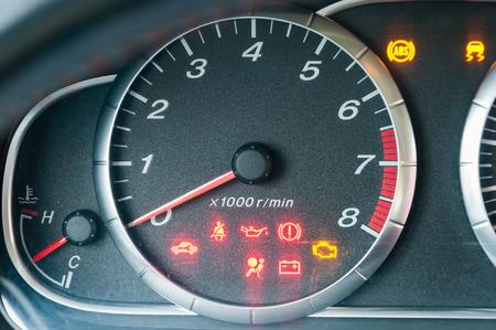 Closeup of car tachometer with many illuminated indicators photo