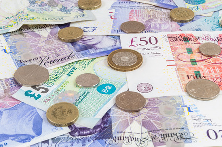 Background made of english pounds banknotes and coins