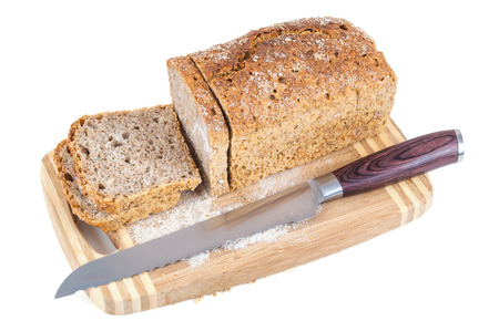 Cut wholemeal bread and knife on a chopping board isolated on white background with clipping path photo