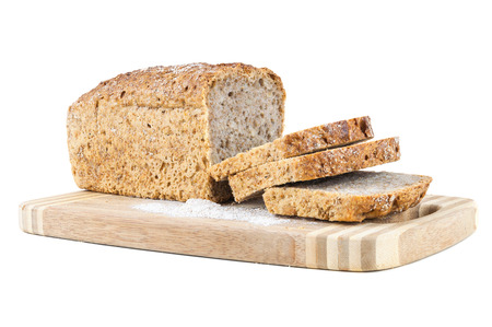 Cut wholemeal bread on a chopping board isolated on white background with clipping path photo