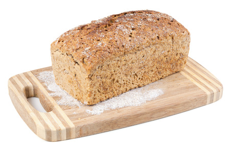 Wholemeal bread on a chopping board isolated on white background with clipping path photo