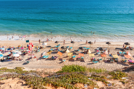 region of algarve: ALBUFEIRA, PORTUGAL - AUGUST 29, 2014: Crowded Falesia Beach seen from the cliff. This beach is a part of famous tourist region Algarve.