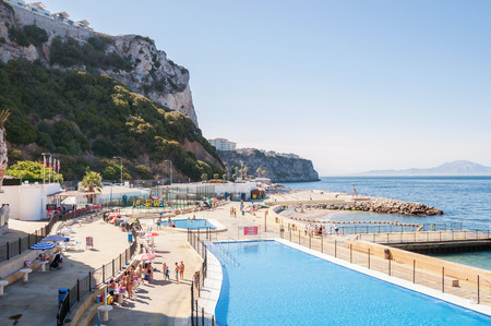 sunbath: GIBRALTAR - AUGUST 27, 2014: People sunbathe at open |air swimming pool in Gibraltar, Aa very popular spot to take a swim and sunbath with access to the sea.