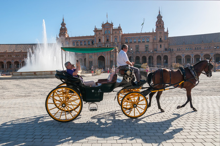 spanish architecture: SEVILLE, SPAIN - AUGUST 28, 2015: Horse carriage with tourists at Plaza de Espana in Seville. It is a landmark example of the Renaissance Revival style in Spanish architecture.