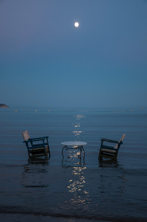 luz de luna: Mesa y dos sillas en el mar para la cena rom�ntica luz de la luna Foto de archivo