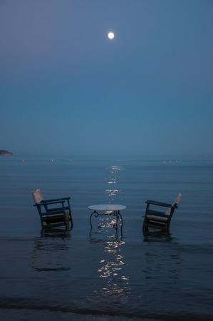 Table et deux chaises dans la mer pour dîner romantique au clair de lune