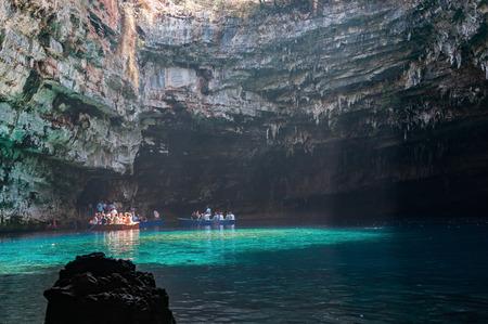kefallonia: Cephalonia, Greece - August 30, 2015: Tourists take a boat trip on the beautiful Melissani Lake.