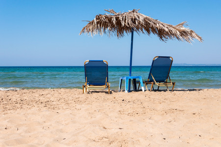 sunbeds: Sunbeds and straw umbrella on Banana beach, Zakynthos, Greece