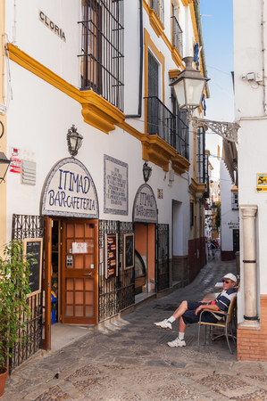 spaniards: Seville, Spain - August 28, 2014: Tourist sits in front of the traditional cafeteria on the narrow street of Seville.