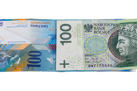 Banknotes of 100 polish zloty and swiss franc isolated on white background