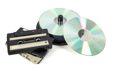 Stacks of CDs on spool and audio tapes isolated on white background