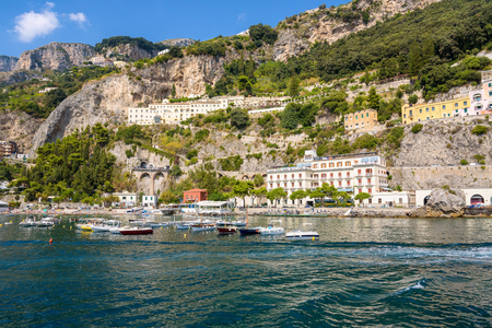 Boats moored at the cliff coast in Amalfi on sunny day