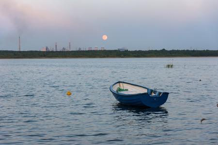 Boat on Pogoria 4 lake at moonrise, Dabrowa Gornicza, Poland Stock Photo