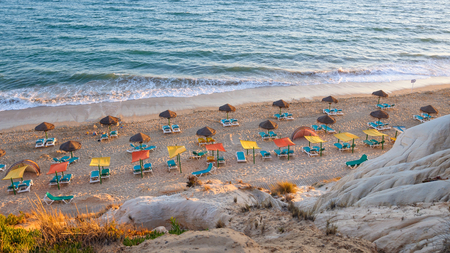 Sunbeds and umbrellas on the Falesia Beach in afternoon sun, Algarve, Portugal Фото со стока