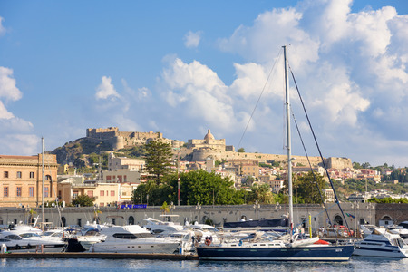 Milazzo, Italy - August 22, 2017: View of the port in Sicilian town with Milazzo Castle in the background Editorial