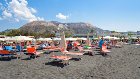 Vulcano Island, Italy - August 22, 2017: People relax on the black volcanic beach on Vulcano Island.