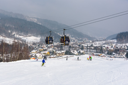 Szczyrk, Poland - February 26, 2018: People skiing at Szczyrk Mountain Resort, with a new 10-seat gondola lift and artificially snow-covered and illuminated ski slopes