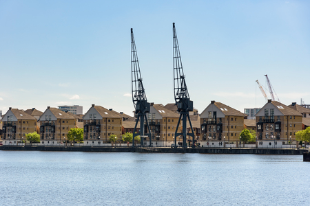 Port cranes and houses at Royal Victoria Dock in London, UK