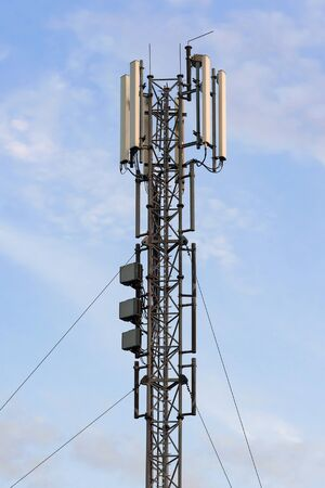 Cellular base station with panel antennas against blue sky