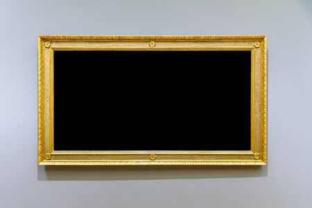 Empty golden picture frame on the gray wall Stockfoto