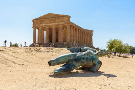 Agrigento, Italy - August 24, 2017: Sculpture of Icarus by Igor Mitoraj in front of the Concordia Temple in Valley of the Temples in Agrigento on Sicily Editorial
